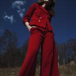 Dziewczyna stojąca na trawie, w tle las, ubrana w czerwone spodnie i czewoną marynarkę