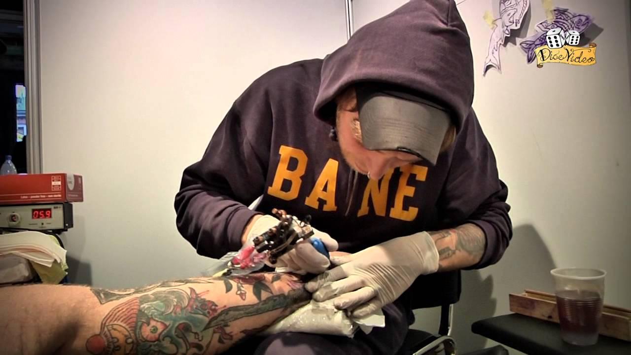 Na zdjęciu znajduje się mężczyzna ubrany w bluzę z kapturem, wykonujący tatuaż osobie leżącej na leżance.