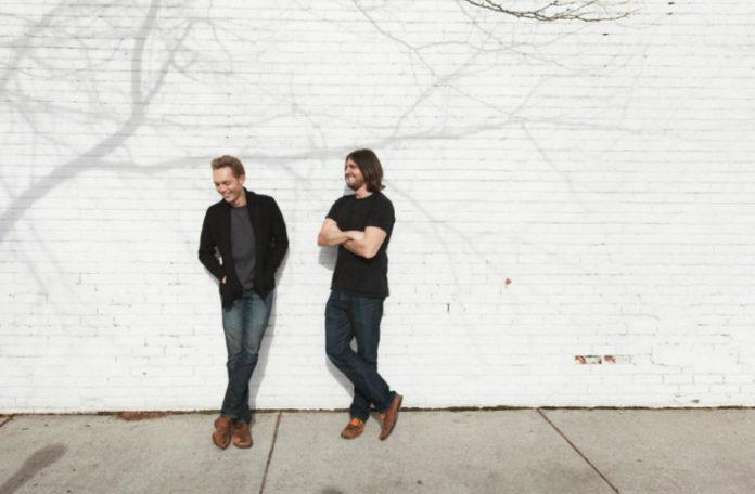 Fotografia kolorowa ukazująca dwóch uśmiechniętych mężczyzn. Mężczyzni opierają się o białą ścinaę z cegieł, na której widać cień gałęzi drzewa. Mężczyzna po lewej stronie ma krótkie blond włosy, czarną rozpiętą kurtkę, niebieską koszulkę i jeansy. Mężczyzna po prawej ma czarne włosy sięgające ramion. Czarną koszulkę i granatowe jeansy.