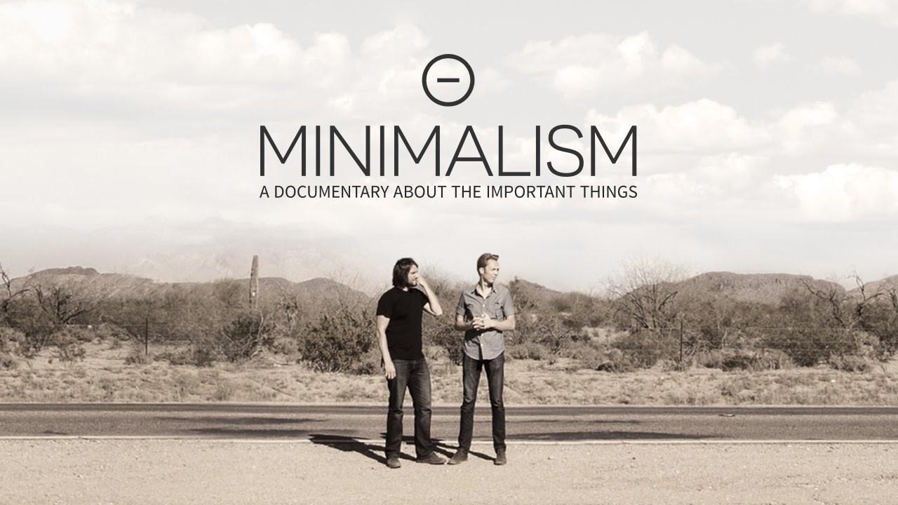 """Fotografia w kolorach sepii. Na środku, wśród pustynnej scenerii stoją dwaj mężczyźni. Obaj zwróceni sa w prawą stronę. Mężczyzna po lewej stronie ubrany jest w czarną koszulkę z krótkim rękawem i zcarne jeansy, ma czarne włosy do ramion. Mężczyzna po prawej ma szarą koszulę z długim rękawem, czarne spodnie i krótkie blond włosy. Nad nimi jest czarny napis: """"Minimalism: A documentary about the important things""""."""