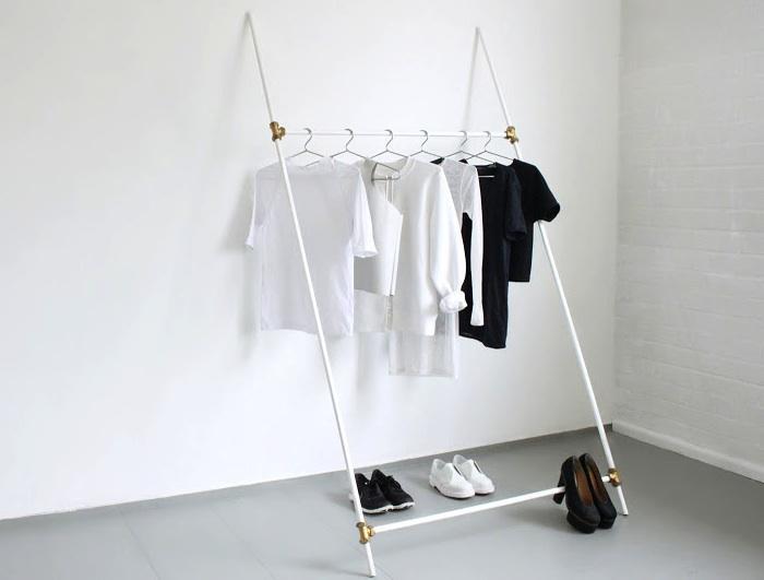 Biała ściana z wieszakiem na którym zawieszonych jest kilka białych i czarnych koszulek