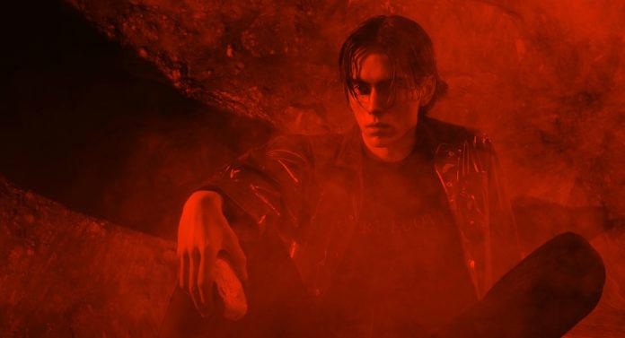 Zdjęcie z czerwonym światłem przedstawiające siedzącego na podłodze mężczyznę z grzywką