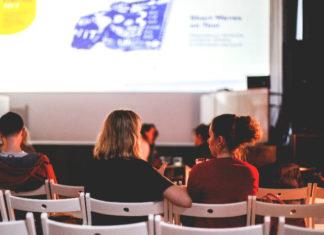Ludzie siedzący na białych krzesłach naprzeciwko ekranu kinowego