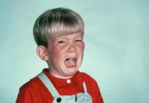 Fotografia kolorowa. Na zdjęciu, na jasno-niebieskim tle widać płaczącego chłopca. Chłopiec ma czerwoną koszulkę polo i jasno-niebieskie jeansowe ogrodniczki. Jasne blond włosy, obcięte są równo, na tak zwanego grzybka.