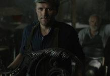 Ciemne zdjęcie przedstawiające mężczyzne w koszulce z krótkim rękawem i kamizelce stojącego przy żelaznym elemencie ozdobnym