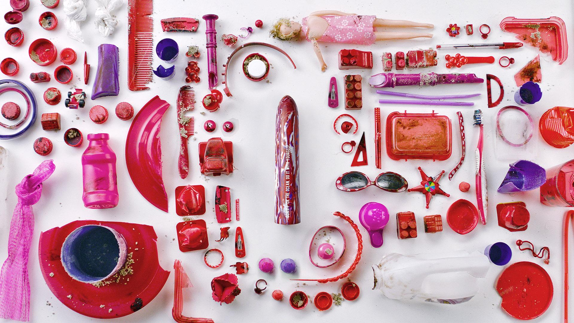 Fotografia reklamowa. Na białym tle ułożone równo sa biało-czerwone śmieci, np. lalka barbie, ekierka, plastikowe części naczyń itp. Po środku leży biało-czerwone dildo.