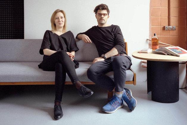 Mężczyzna i kobieta ubrani na szaro-czarno siedzący na szarej kanapie
