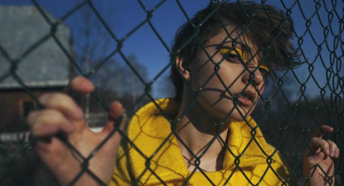 Dziewczyna w żółtym płaszczu i żółtych kreskach na powiekach, trzyma rękami za ogrodzenie z siatki