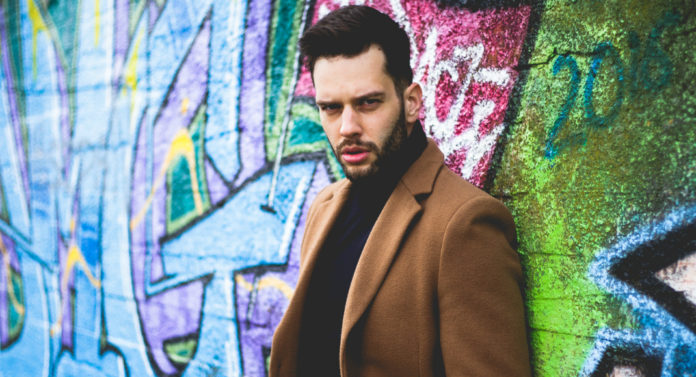 Mężczyzna ubrany w czarny golf i brążowy płaszcz opiera się o ścianę z kolorowym graffiti