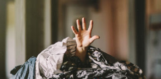 Fotografia kolorowa ukazująca wystająca spoza sterty kolorowych ubrań męską rękę.