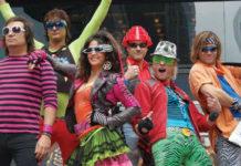Grupa ludzi ubrana w imprezowe ubrania w stylu lat 90.