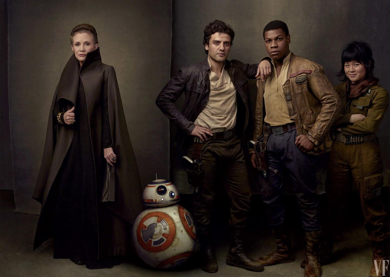 Fotografia kolorowa utrzymana w kolorach brązu. Na zdjęciu widać pięć postaci z filmu Gwiezdne Wojny. Po lewej stronie stoi księżniczka Leia, ubrana w długi, brązowy płaszcz z postawionym kołnierzem, pod spodem ma czarną długą suknię, na głowie ma zaplecione włosy w warkocz, który owinięty jest wokół głowy. Obok niej stoi biały robot z pomarańczowymi okręgami. Robot wygląda jak połączone dwie kulki, z czego głowa jest mniejsza. Następny jest mężczyzna z ciemnymi kręconymi włosami, ubrany w kremową koszulę i ciemną skórzaną kurtkę, spodnie ma ciemnobrązowe, następny jest czarnoskóry mężczyzna z krótkimi czarnymi włosami. Ubrany w kremową koszulę, jasnobrązową skórzaną kurtkę i granatowe spodnie, ma też pasek z prostokątną klamrą. Ostatnia jest niska kobieta, azjatka. Ma ciemne włosy sięgające brody i grzywkę. Na szyi ma brązową chustę, ubrana jest w ropboczy kombinezon w kolorze zgniłej zieleni a przez talię ma przepasany pas z nabojami.