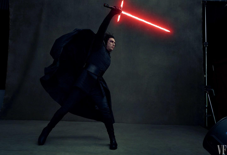 Fotografia kolorowa utrzymana w ciemnych kolorach. Na ciemnym tle widać mężczyznę w czarnym stroju z powiewającym czarnym płaszczem. Mężczyzna stoi bokiem, w pozycji walczącej. Prawa ręka, uniesiona w górę trzyma miecz świetlny o czerwonym kolorze.