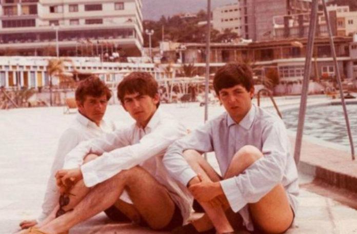 Na zdjęciu widzimy trzech muzyków siedzących na ziemi, podpierających swoje kolana. Ubrani są w białe koszule. W oddali widzimy krajobraz nadmorskiego miasta.