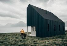 Fotografia kolorowa. Zdjęcie pokazuje mały, czarny, drewnainy domek o spadzistym dachu. Dom usytuowany jest w malowniczej scenerii, w oddali za mgłą widać góry, a na pierwszym planie zieloną trawę. Po lewej stronie domu widać mężczyznę, ubranego w czarne spodnie i żółtą kurtkę, z kapturem na głowie. Mężczyzna idzie w stronę domku.