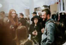 Kilku ludzi stojących w przestrzeni, na pierwszym planie mężczyzna w jeansowej koszuli z plecakiem, obok dziewczyna w ciemnym kapeluszu