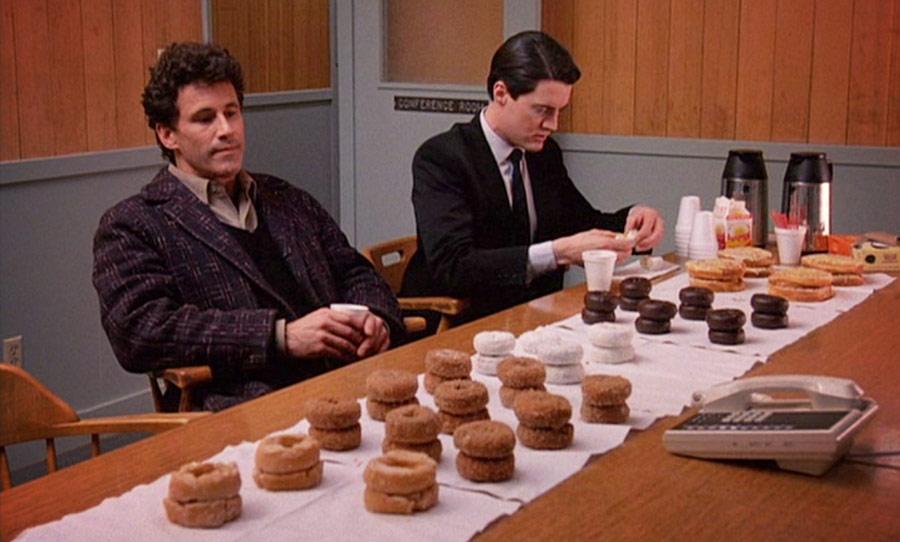 Dwoch mezczyzn siedzi na komisariacie przy stole pelnym paczkow