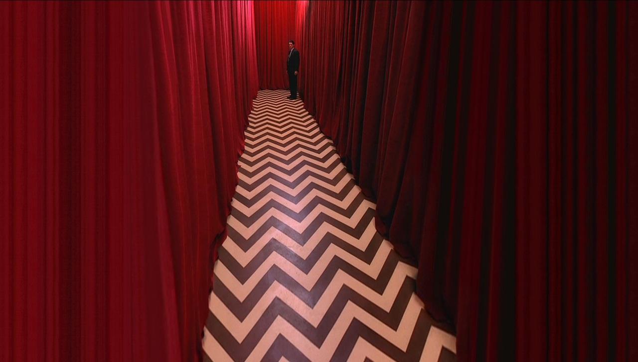Pomieszczenie w ktorym zamiast scian sa krwisto czerwone kurtyny po srodku jest podloga w czarno biale zygzaki a na koncu drogi stoi mezczyna ubrany w garnitur