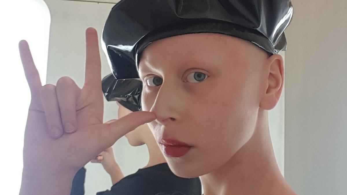 Portret lysej, bladej dzieczyny bez brwi i rzes, pomalowane na czerwono usta, na glowie ma czarny skorzany beret, ubrana w czarny tshirt, palcami trzyma nos i pokazuje znak szatana w tle odbija sie jej tylne odbicie w lustrze