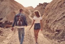 Chłopak ubrany w kurtkę jeansową i dziewczyna w szortach i białej koszulce idą po skalisto-piaskowym terenie
