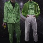 Dwóch chłopaków stojących na gwiaździstym tle, jeden ubrany w zielony golf, drugi w czarną koszulkę i zieloną marynarkę