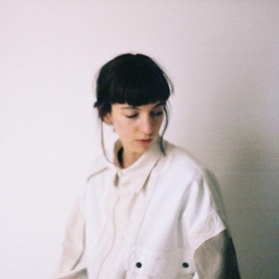 Na bialym tle portret mlodej kobiety o ciemnych wlosach ubranej w jasna duza koszule jej wzrok skierowany jest w lewy bok ciemne wlosy spiete sa z tylu