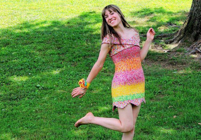 Na zdjęciu widzimy artystkę, która prezentuje sukienkę wykonaną z opakowań po cukierkach. Stoi na tle trawy i uśmiecha się.