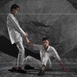 Dwóch chłopaków, jeden siedzący na ziemi, drugi wyciągający do niego dłoń, obaj ubrani w srebrne ubrania