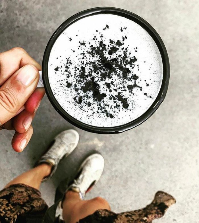 Na zdjęciu jest kawałek dziewczyny, która trzyma kubek z kawą latte. Kawa jest biała ale posypana jest sproszkowanym węglem aktywnym.