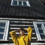 Dziewczyna w żółtym płaszczu, trzymająca dłonie na głowie stoi na tle drewnianego domu
