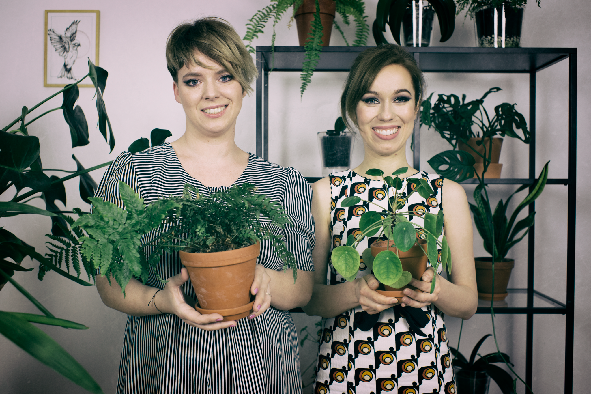 Dwie dziewczyny: brunetka i blondynka, trzymające w dłoniach doniczki z kwiatami