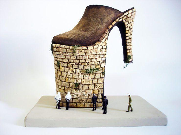 Rzeźba przypominająca but na wyższym od obcasa koturnie. Na dole koturna stoją małe ludziki