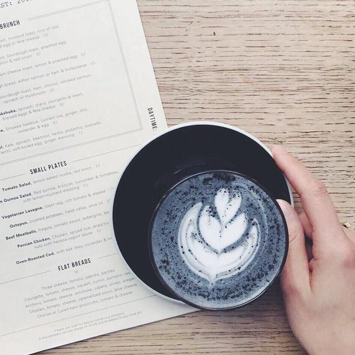 Na zdjęciu jest ciemna kawa latte w czarnej filiżance. Widać rękę dziewczyny, która trzyma talerzyk, na którym stoi kawa. Obok leży kartka zapisanego papieru.