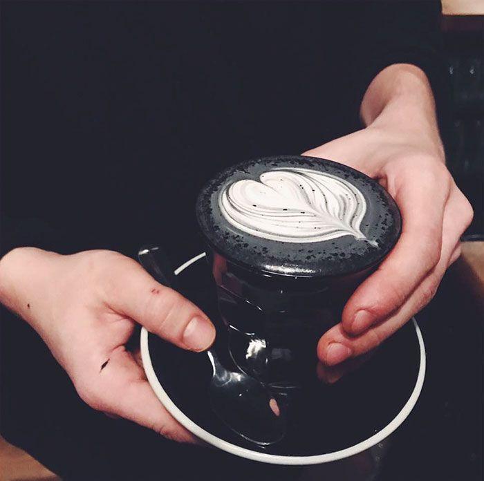 Na zdjęciu widzimy kawałek ciemno ubranej dziewczyny, która trzyma ciemny talerzyk i czarną filiżankę, w której jest ciemna kawa latte.
