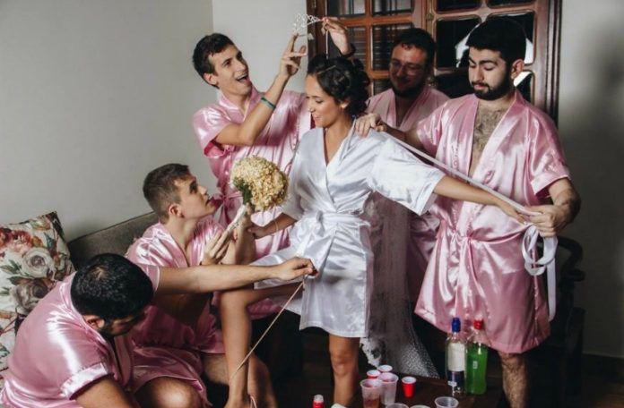 pieciu mezczyzn w rozowych szlafrokach i kobieta w bialym szlafroku