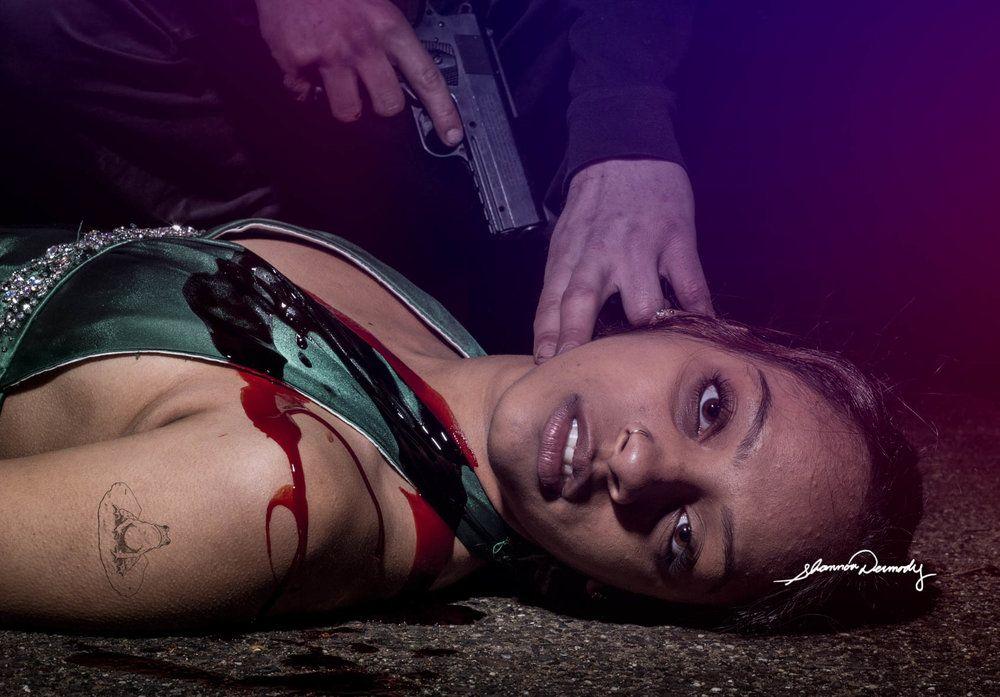 kobieta lezaca na podlodze z pistoletem przy glowie