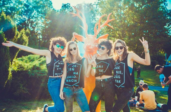 Cztery dziewczyny ubrane w takie same czarne podkoszulki stoją na dworze, w tle rzeźba jelenia
