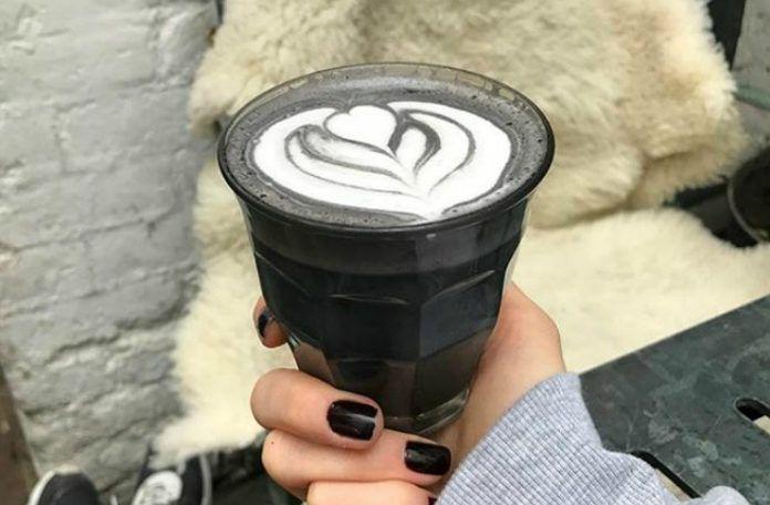 Dłoń z pomalowanymi na czarno paznokciami trzyma w szklankę z czarną kawą