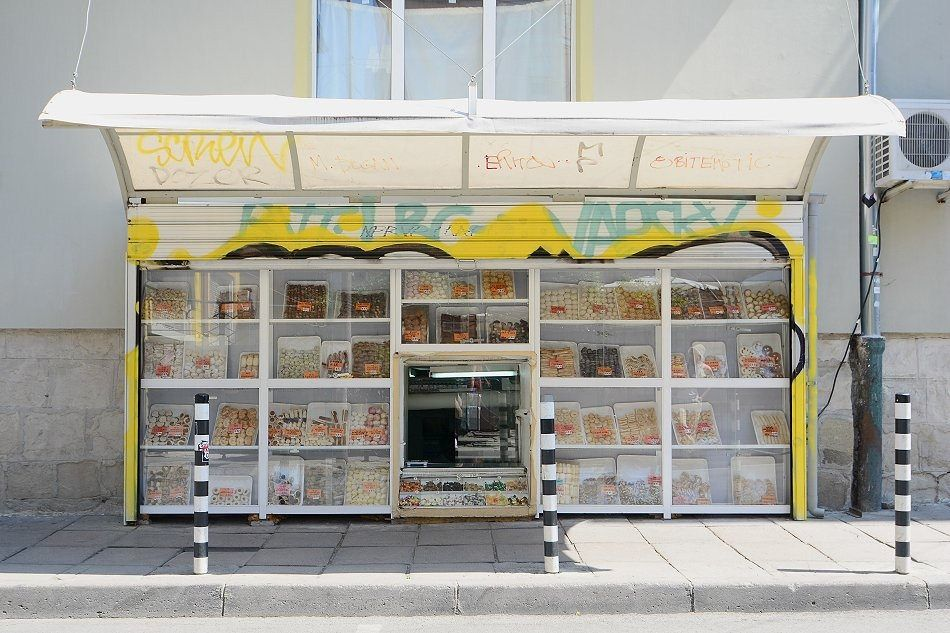 """Zdjęcie przedstawia budynek, w który wkomponowana jest cukiernia. Okienko do płacenia znajduję się kilkadziesiąt centrymetrów nad chodnikiem. Dookoła znajdują się półki z ciastkami oraz cukierkami. Nad """"kioskiem"""" umocowana jest biała markiza."""