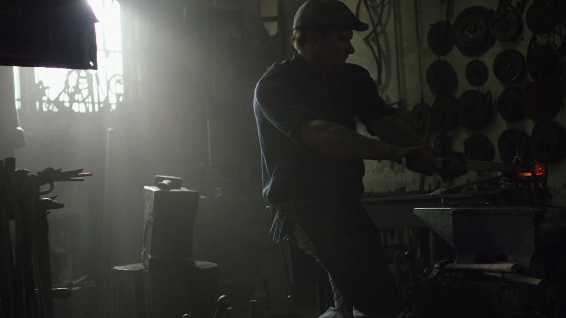 Mężczyzna wykuwający w żelazie macha ręką