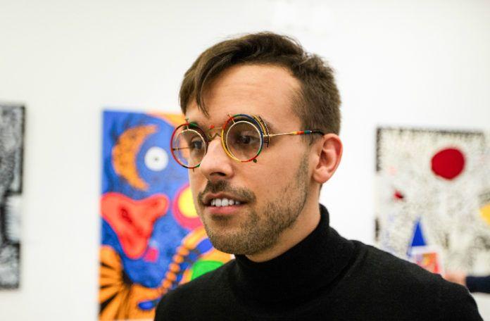 Mężczyzna ubrany w czarny gold i kolorowe okrągłe okulary