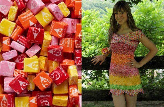 Na zdjęciu widać dziewczynę, która ma na sobie krótką, kolorową sukienkę stworzoną z papierków po cukierkach. Opiera się o płot w lesie i jest uśmiechnięta, a obok cukierki Starburst