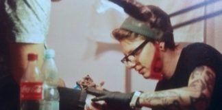 Na zdjęciu znajduje się mężczyzna wykonujący tatuaż na nodze człowieka siedzącego na leżance