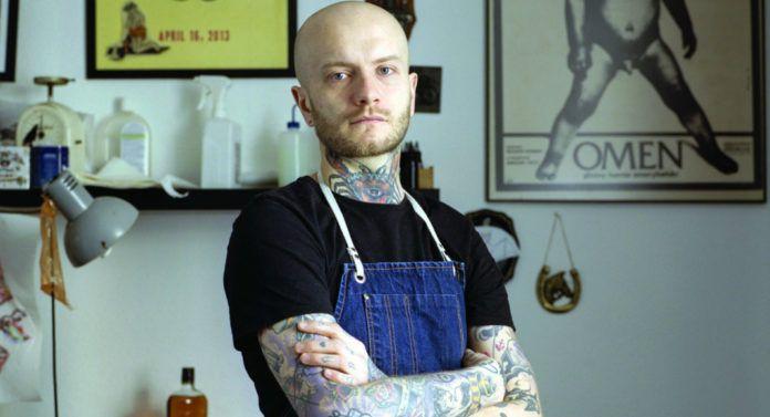 Mężczyzna w czarnej koszulce i roboczym fartuchu z tatuażami na rękach i szyi