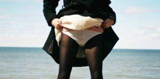 Zdjecie zrobione jest na skarpie nad morzem widac na nim dziewczyne od pasa w dol ubrana jest w czarne rajstopy jej nogi sa chude a dlonie podnosza biala spodnice i ukazuja sie nam biale majtki z haftem golej kobiety