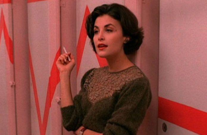 Brunetka w krotkich wlosach ubrana w zielony sweter ma podwiniete rekawy i stoi w damskiej toalecie z rozowymi scianami palac papierosa