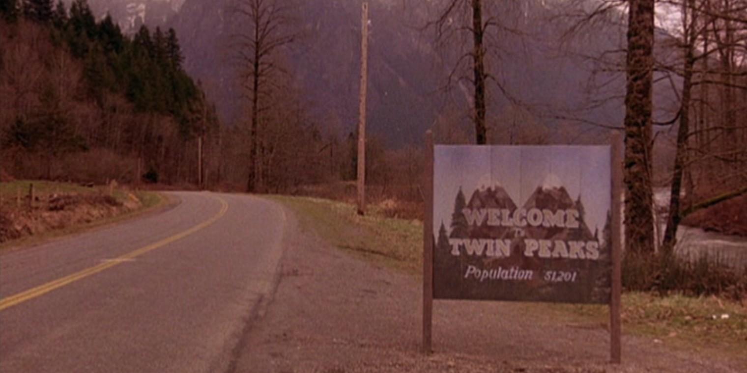 Wjazd do miasteczka na tablicy widzimy napis Welcome To Twin Peaks Po lewej stronie znajduje sie ulica a po prawej drzewa i zielona trawa