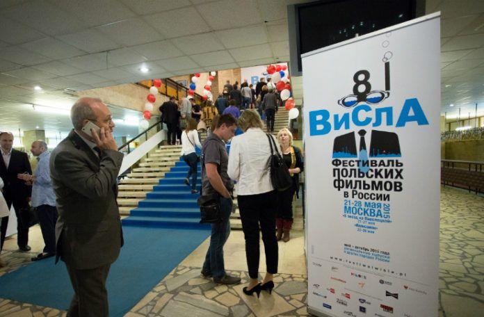Ludzie stojący w pomieszczeniu, na pierwszym planie plakat Festiwalu Filmowego Wisła