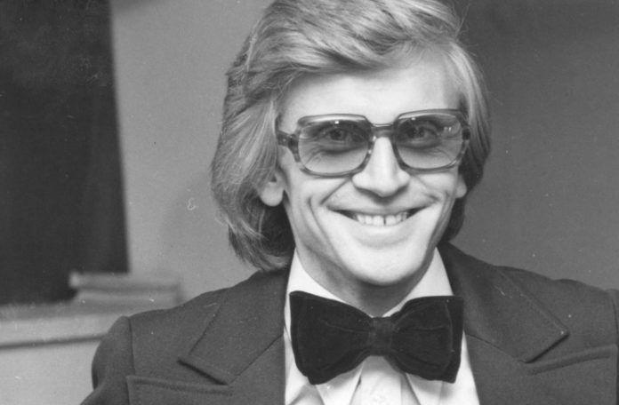 Czarno-białe zdjęcie mężczyzny w garniturze i muszce, w okularach na twarzy, uśmiechnięty