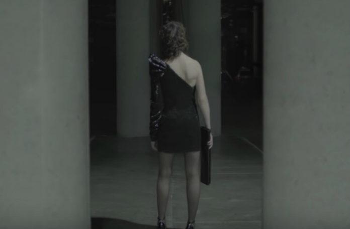 Na czarno bialym zdjeciu widzimy odwrocona do nas tylem dziewczyne w asymetryczne sukience mini bez prawego rekawa, na czarnobialym zdjeciu stoi w magazynie w walecznej pozycji na srodku zdjecia widnieje napis saint laurent